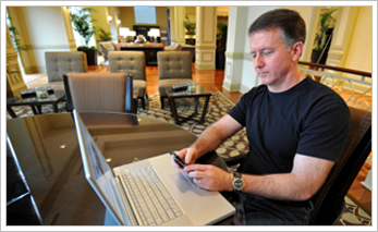 Hotel customer sitting using a computer accessing the internet from hotel wireless connection